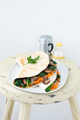 A tortilla filled with spinach and mushrooms