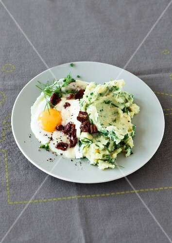 Mashed potatoes with herbs, a fried egg and dried tomatoes