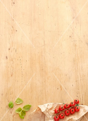 Fresh basil and vine tomatoes on a wooden surface