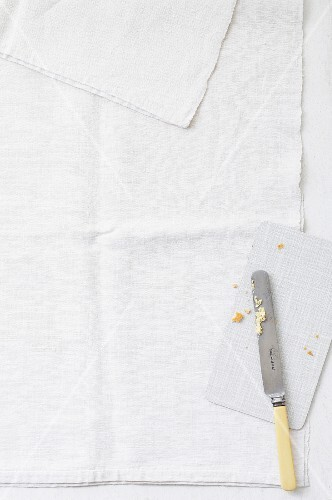 A used board and a knife on a linen cloth (seen from above)