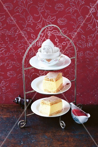 Cream slices with raspberry sauce on a cake stand