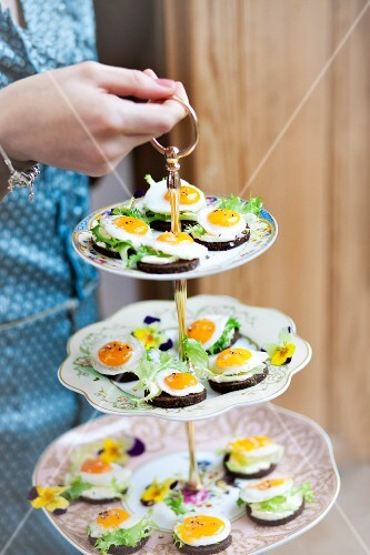 Fried eggs on pieces of pumpernickel on a cake stand