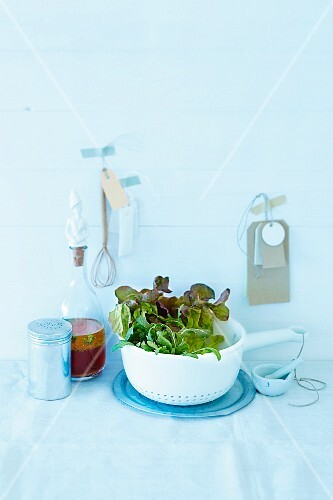 Lettuce in a sieve next to a bottle of dressing