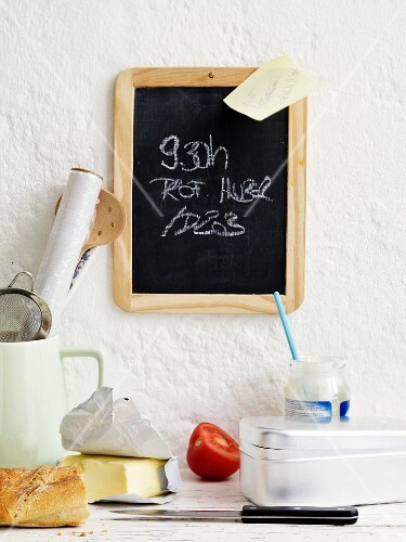 Writing on blackboard & ingredients for packed lunch in students' kitchen