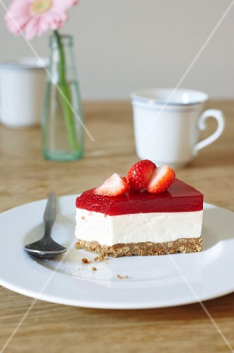 Slice of creamy cheesecake topped with strawberry purée with vodka