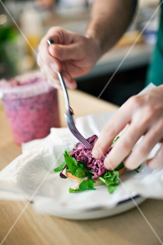 A burger with lettuce and red cabbage being made