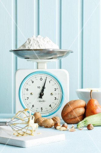 An arrangement of baking ingredients and a pile of flour on an old pair of kitchen scales