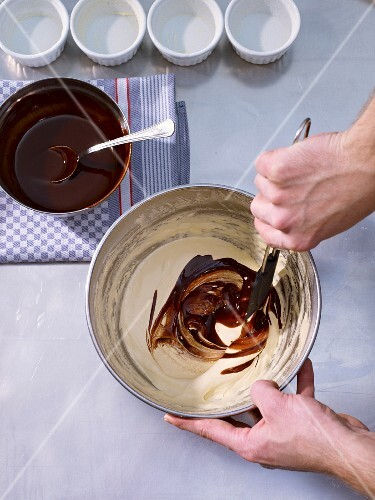 Butter and chocolate mixture being added to an egg yolk-sugar mixture
