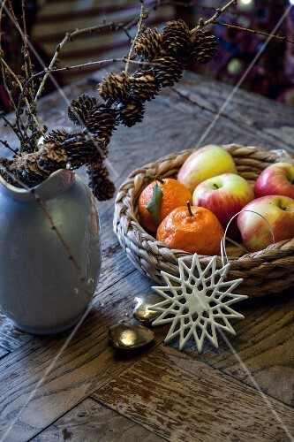 A basket of fruit next to a vase with larch twigs