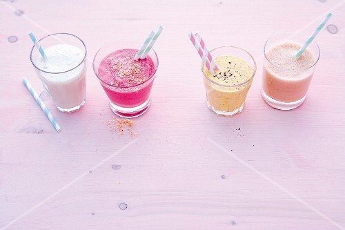 Four healthy smoothies in glasses with straws