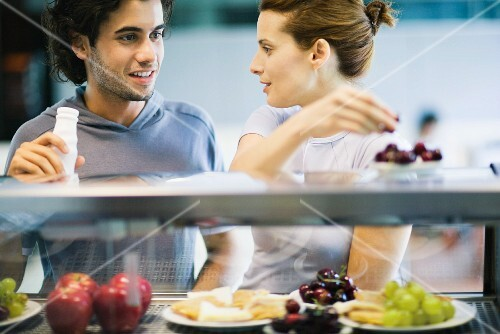 Two young adults standing at snackbar, chatting