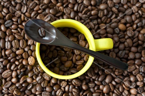 An espresso cup and a spoon on a pile of coffee beans