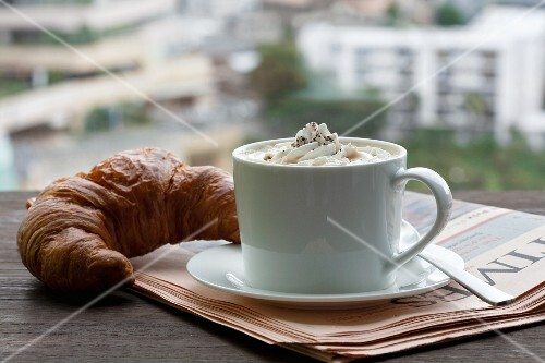 A cappuccino with a croissant on newspaper in front of a window