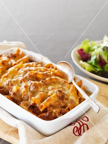 Gratinated penne pasta with bolognese sauce and cheese in a baking dish