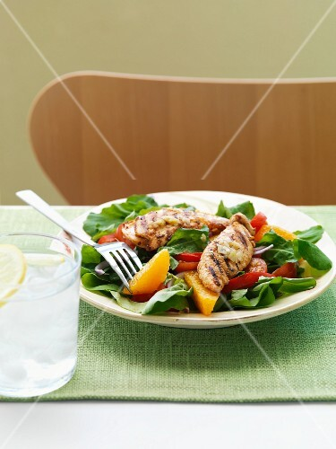 Salad with orange wedges with chicken breast strips
