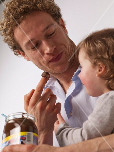 Father and daughter nibbling chocolate spread