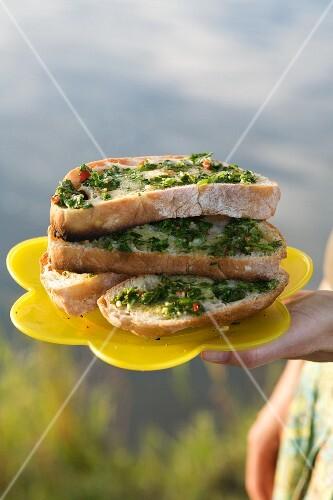 Herb bruschetta on a yellow plastic plate