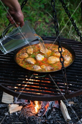 Water being added to a pan of paella being cooked on an open fire