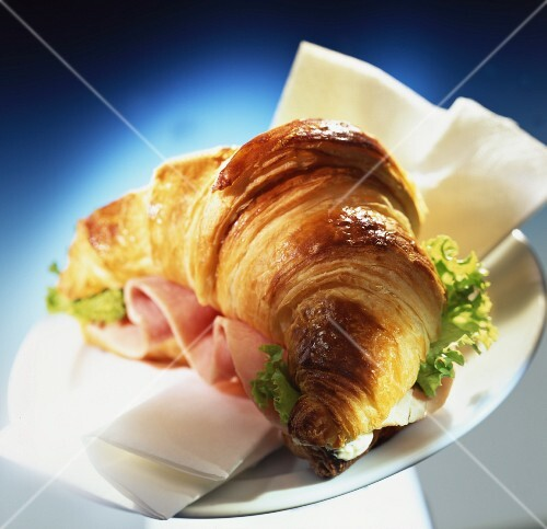 A croissant with ham and lettuce