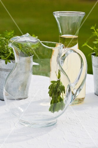 A bunch of woodruff in a jug and a carafe of white wine