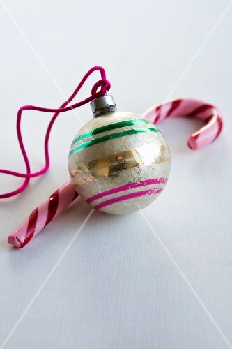 A Christmas tree bauble and a candy cane