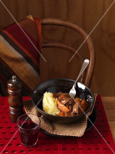 Braised lamb with mashed potatoes on a table with wine