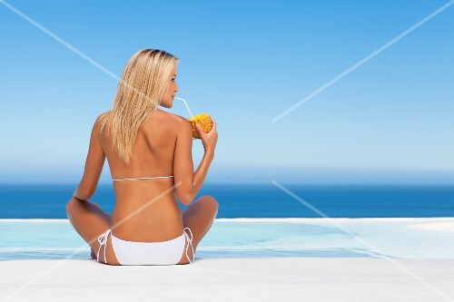 Woman drinking from pineapple by pool