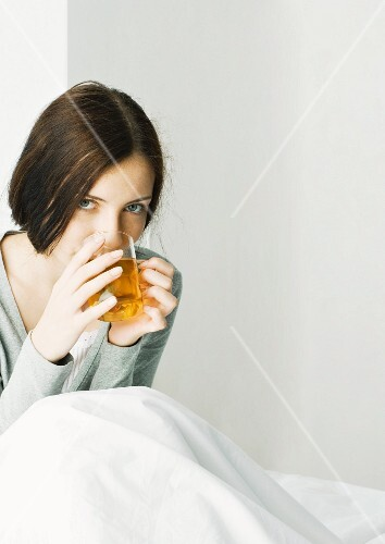 Young woman sitting under covers, drinking hot tea