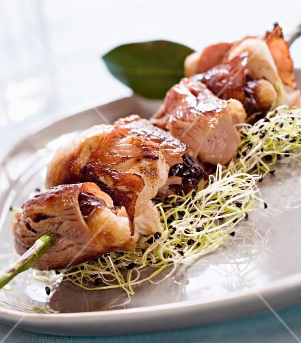 Chicken kebab with bacon and dried plums on a bed of bean sprouts