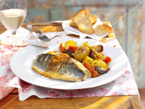 Sea bass fillets with vegetables and a glass of white wine
