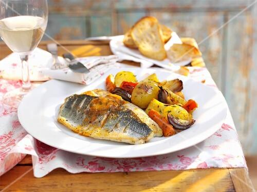 Seebarschfilets mit Gemüse, dazu ein Glas Wein