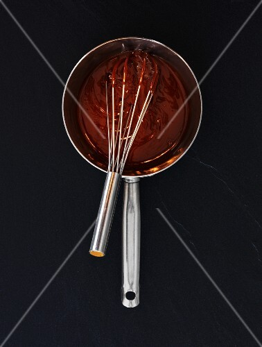 Liquid chocolate in a saucepan with a whisk (seen from above)