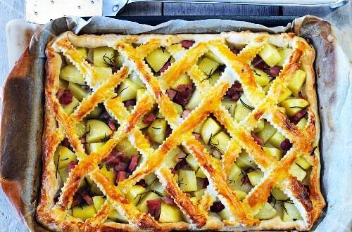 A lattice potato and ham pie on a baking tray