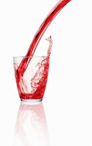 A red fizzy drink being poured into a glass