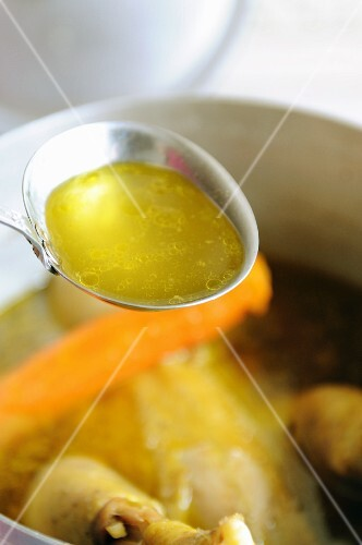 A ladle of chicken broth above a pot of soup