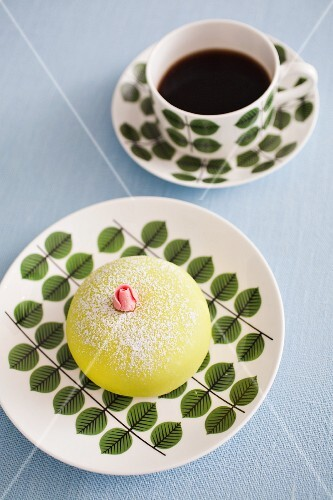 A marzipan cake with a rose bud and a cup of coffee (Sweden)