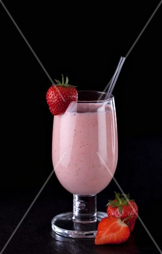 A strawberry smoothie with fresh strawberries