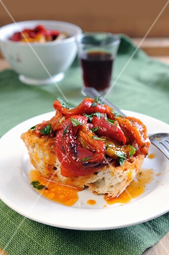 Sweet red and yellow peppers in a spicy chili sauce on a bruschetta