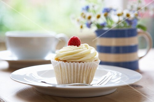 A white chocolate cream and raspberry cupcake