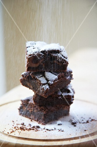 A stack of brownies being dusted with icing sugar