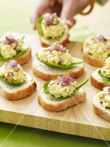 Slices of Bread Topped with Egg Salad on Baby Spinach Leaves