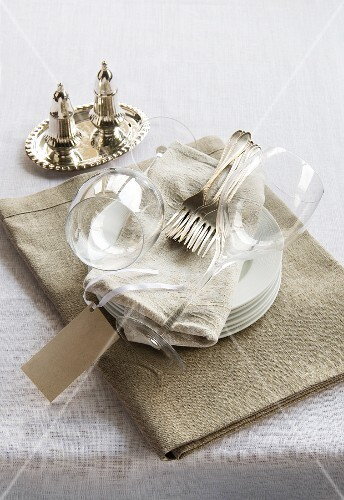 A stack of plates topped with forks and wine glasses