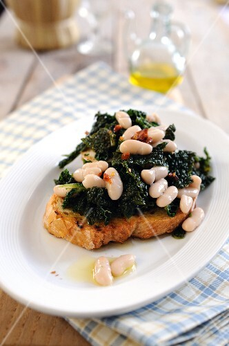 Bruschetta topped with black cabbage and white beans