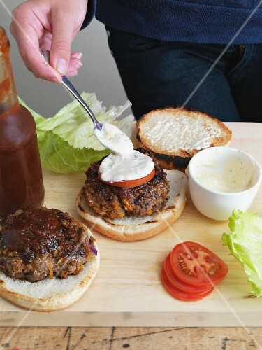 A hamburger being spread with remoulade