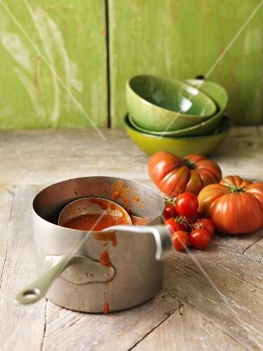 Saucepan of tomato soup on table