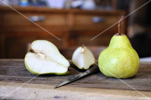 Williams pears, whole and halved, on a wooden board