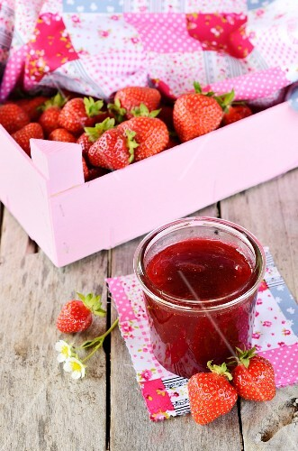 A jar of strawberry jam and fresh strawberries