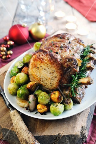 Roast joint of pork on the bone with Brussels sprouts, chestnuts and onions – Christmas roast