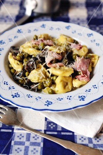 Cheese filled tortelli with a creamy ham, mushroom and pea sauce topped with parmesan cheese