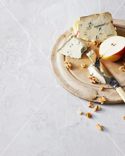 Fruit, cheese and nuts on wooden board